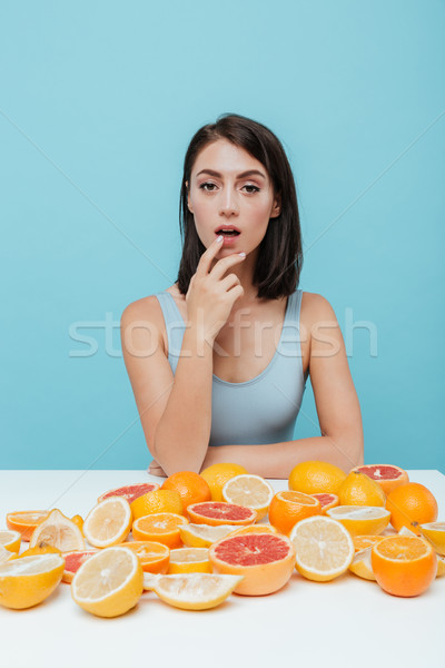 Woman with oranges and grapefruits touching her lips Stock photo © deandrobot