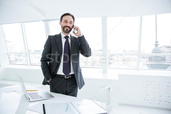 Elderly bearded business man talking at phone Stock photo © deandrobot