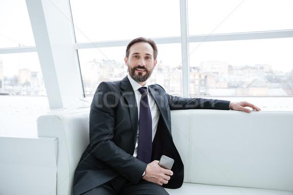 Elderly bearded business man with phone near the window Stock photo © deandrobot