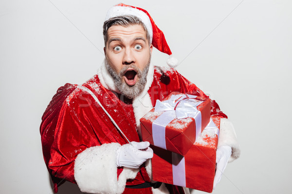 Astonished man santa claus with persent boxes and gift sack Stock photo © deandrobot