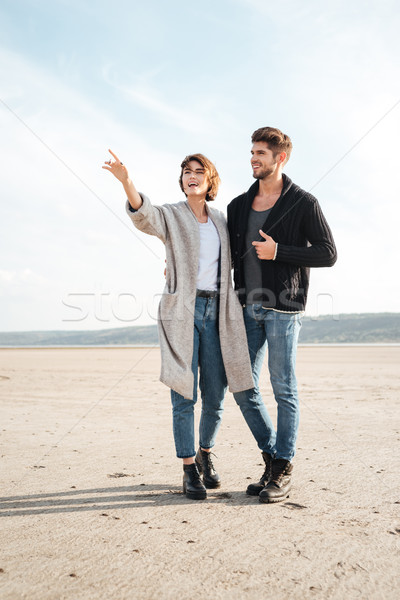 Cheerful young couple standing at the seashore and pointing away Stock photo © deandrobot