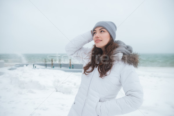 Attractive young lady wearing hat walking near beach Stock photo © deandrobot