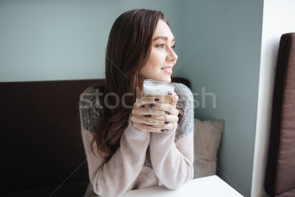 Cheerful young woman sitting in cafe and having a breakfast Stock photo © deandrobot