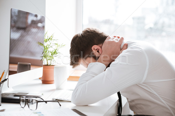 Tired young businessman with painful feelings holding neck. Stock photo © deandrobot