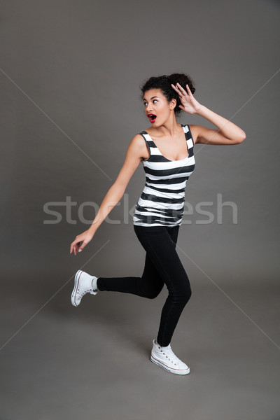 Full length of scared african american young woman running away Stock photo © deandrobot