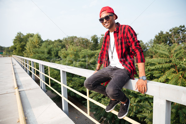 Happy dark skinned guy wearing sunglasses Stock photo © deandrobot