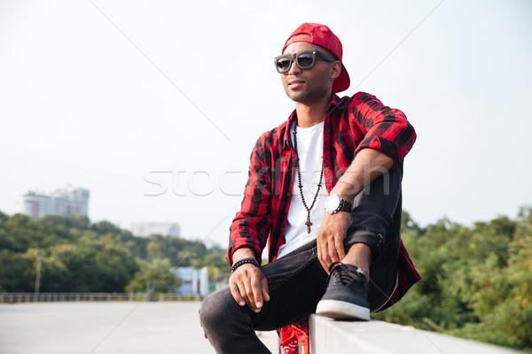 Attractive dark skinned man wearing sunglasses Stock photo © deandrobot