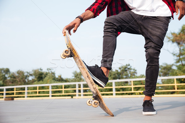 Cropped photo of young dark skinned man skateboarding Stock photo © deandrobot