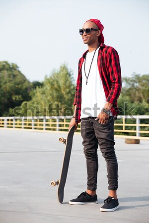 Happy dark skinned young guy sitting near his skateboard Stock photo © deandrobot