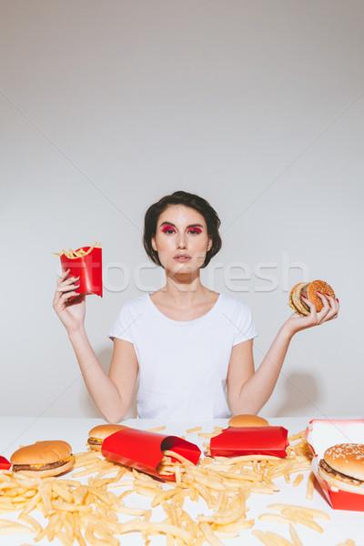 Piękna młoda kobieta frytki hamburger biały Zdjęcia stock © deandrobot