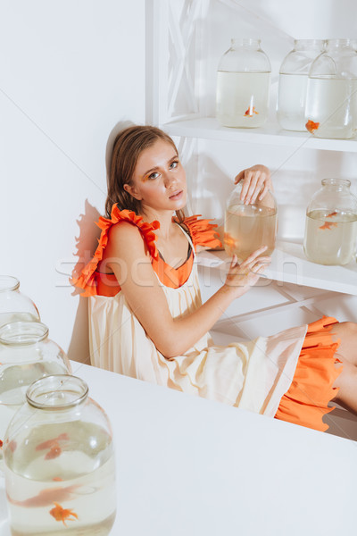 Pretty young woman sitting and holding gold fish in jar Stock photo © deandrobot