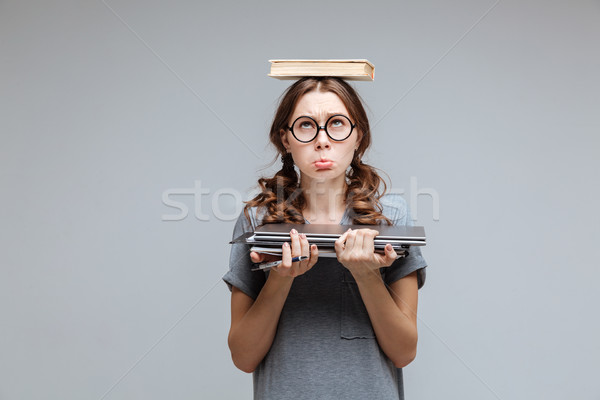 Upset Female nerd with book on head Stock photo © deandrobot