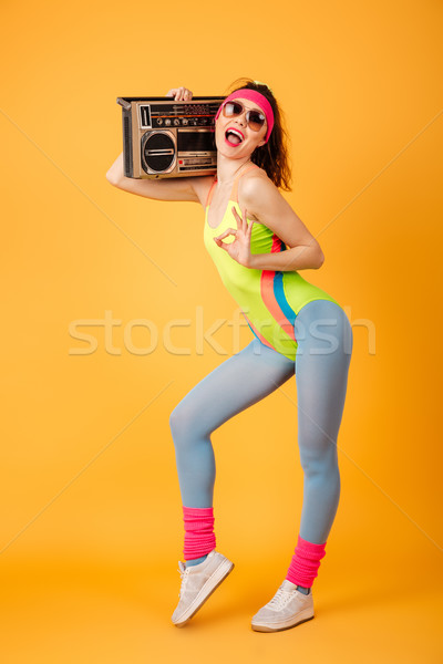 Cheerful pretty young sportswoman holding boombox and showing ok sign Stock photo © deandrobot