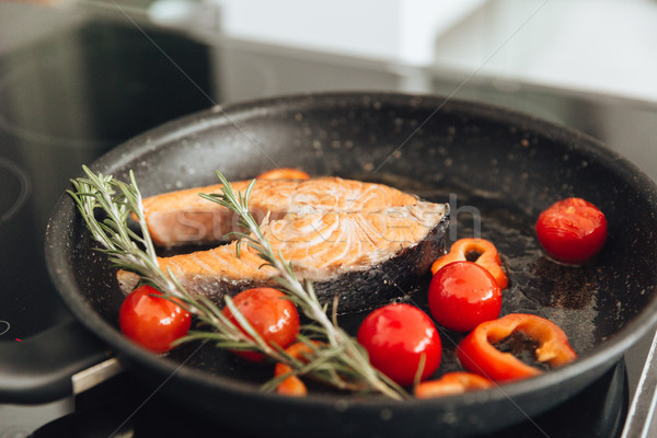 Fish and vegetables on frying pan in kitchen Stock photo © deandrobot