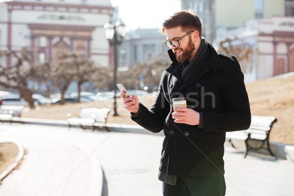 Derűs férfi mobiltelefon áll iszik kávé Stock fotó © deandrobot