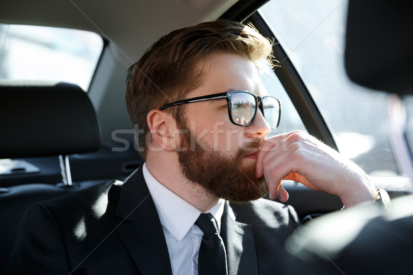 Thoughtful young businessman in eyeglasses holding hand on chin Stock photo © deandrobot