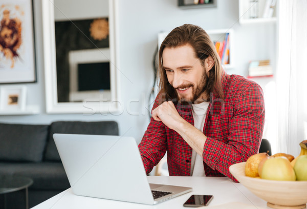 Smiling bearded young man using laptop at home Stock photo © deandrobot