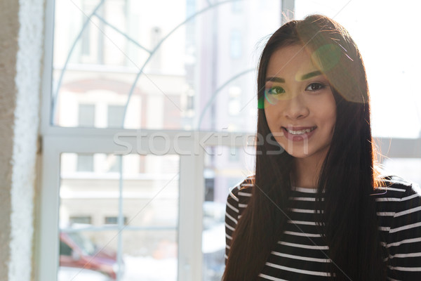 Smiling Asian woman near the window in cafeteria Stock photo © deandrobot