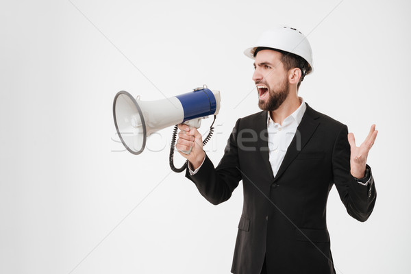 Screaming architect wearing helmet talking with loudspeaker. Stock photo © deandrobot