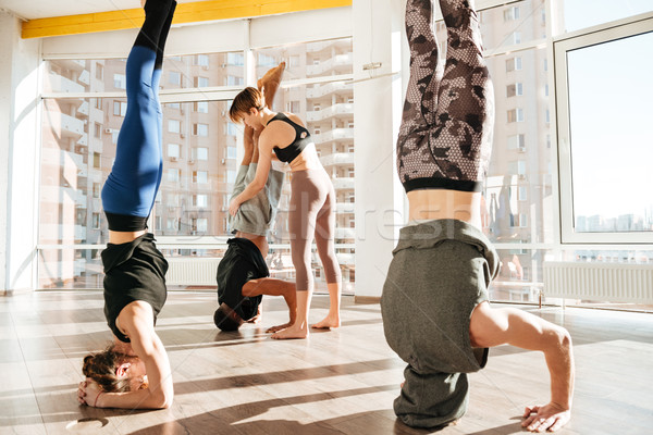 Group of people working out with instructor and doing headstand Stock photo © deandrobot