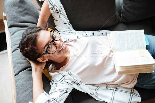 Happy african woman wearing glasses reading book. Stock photo © deandrobot