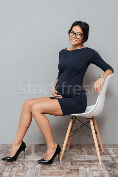 Derűs terhes üzletasszony ül zsámoly kép Stock fotó © deandrobot