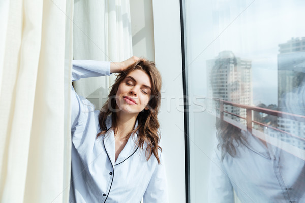 Amazing young lady standing at home near window and posing Stock photo © deandrobot