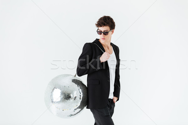 Side view of man in suit carrying disco ball Stock photo © deandrobot