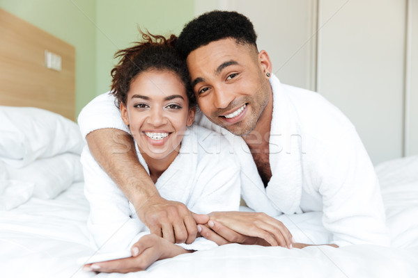 Happy young african loving couple on bed Stock photo © deandrobot