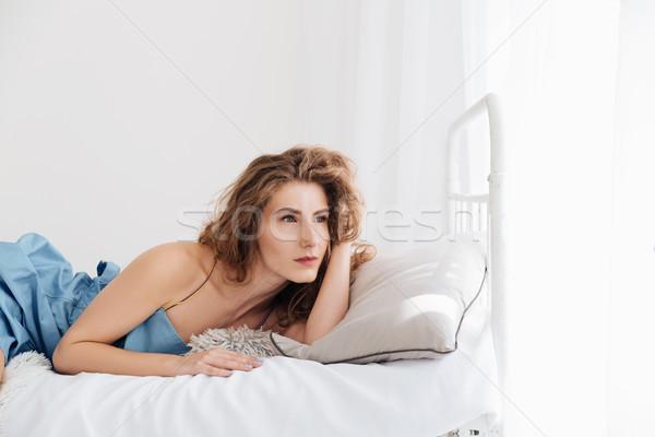 Mujer mentiras cama mirando imagen Foto stock © deandrobot