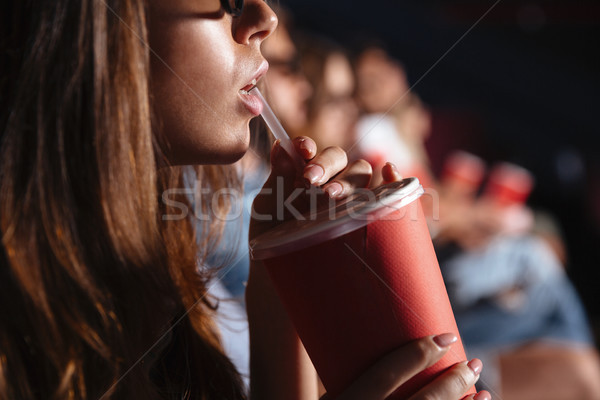 Cropped picture of young lady sitting in cinema Stock photo © deandrobot
