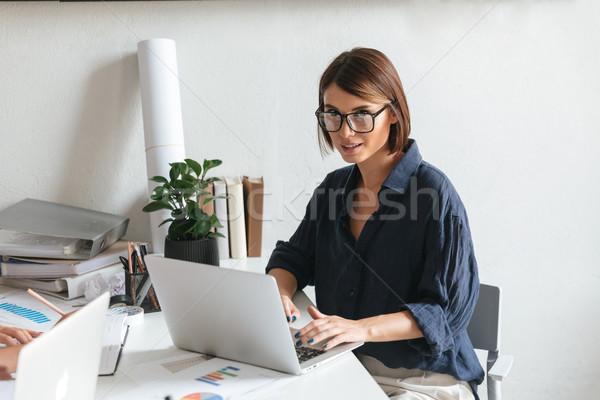 Calm beauty woman in eyeglasses using laptop computer Stock photo © deandrobot