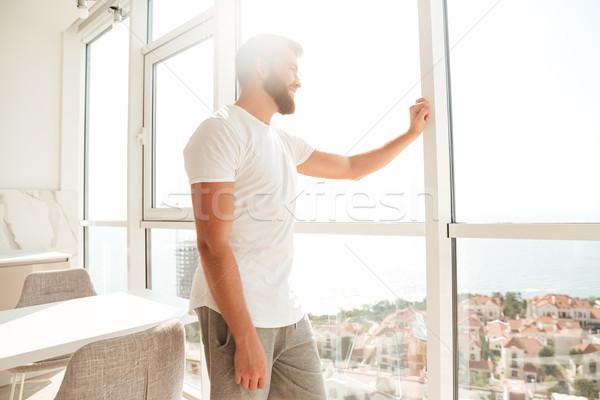 Zijaanzicht knap bebaarde man naar venster Stockfoto © deandrobot