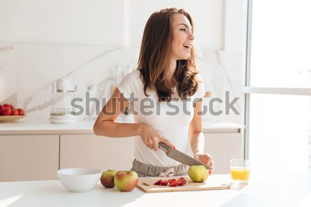 Happy healthy woman cutting fruits on a wooden board Stock photo © deandrobot