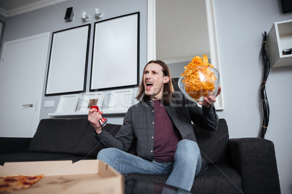 Screaming man sitting at home indoors eating crisps Stock photo © deandrobot