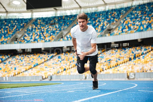 Young male athlete running on a racetrack Stock photo © deandrobot