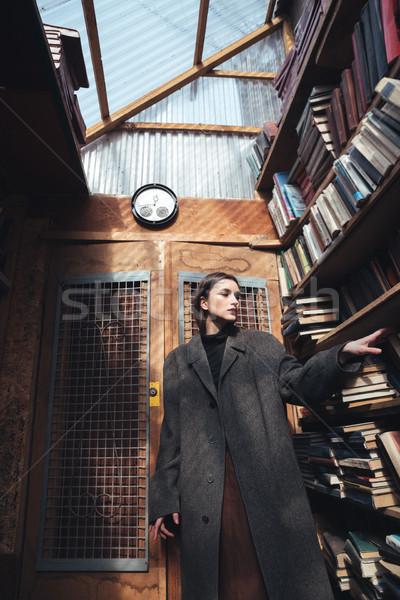 Alla moda donna cappotto libro shelf Foto d'archivio © deandrobot