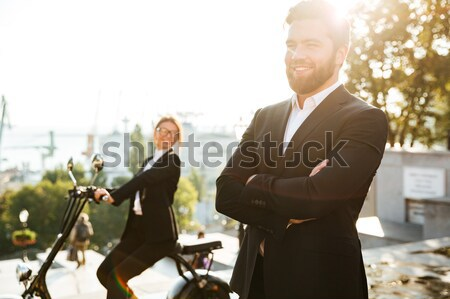 Carefree business man posing outdoors using smartphone Stock photo © deandrobot