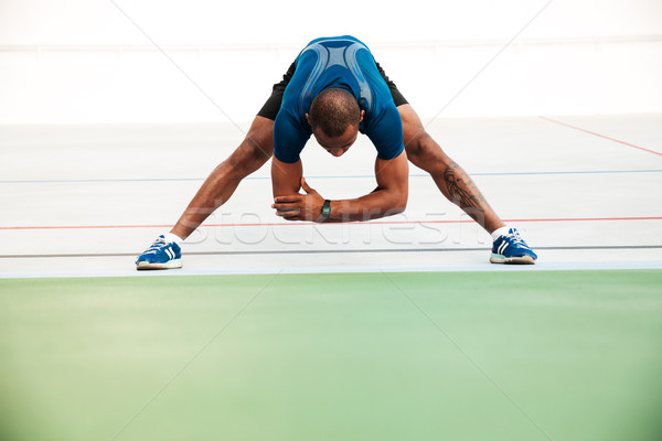 Full length portrait of a young sportsman doing stretching Stock photo © deandrobot