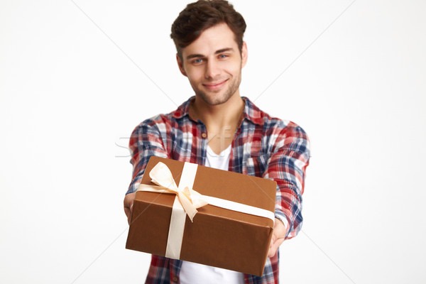 Portrait of an attractive happy man showing present box Stock photo © deandrobot