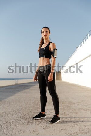 Stock photo: Young fitness lady making stretching exercises near sea