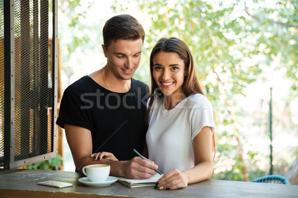 Smiling young couple making notes in a textbook together Stock photo © deandrobot