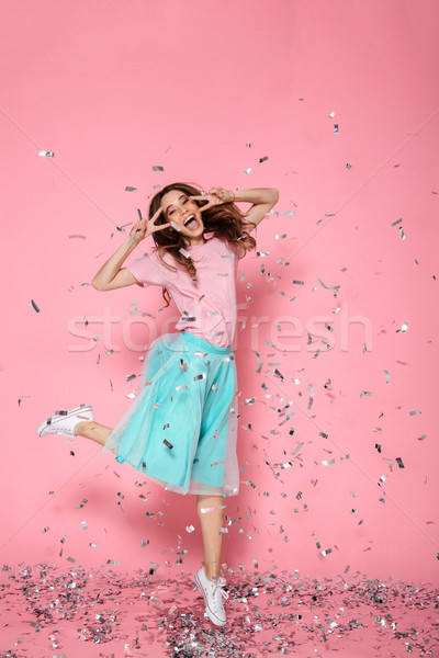 Full length photo of pretty young woman showing peace gesture an Stock photo © deandrobot
