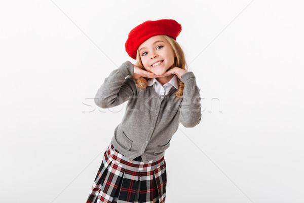 Portrait of a smiling little schoolgirl dressed in uniform posing Stock photo © deandrobot