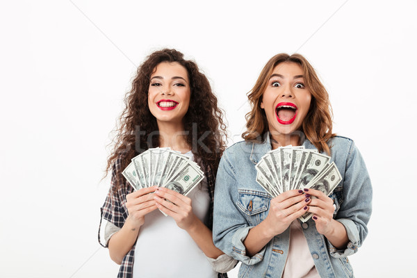 Two happy girls holding money and rejoices Stock photo © deandrobot
