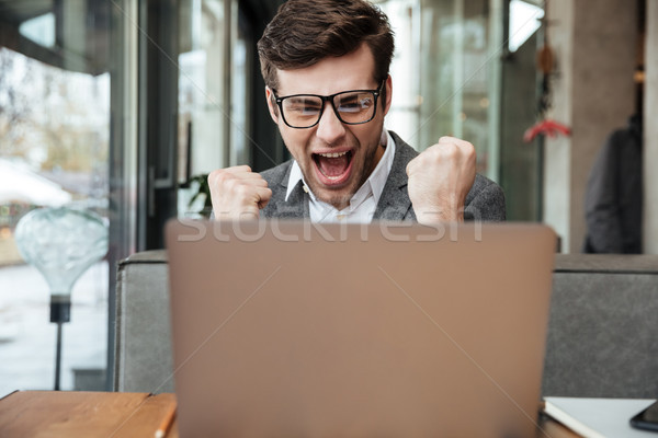 Pleased screaming business man in eyeglasses sitting by the table Stock photo © deandrobot