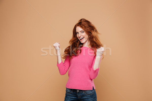 Portrait of a joyful satisfied redhead girl celebrating Stock photo © deandrobot