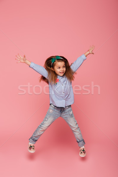 Full-length picture of joyful carefree child jumping and throwin Stock photo © deandrobot