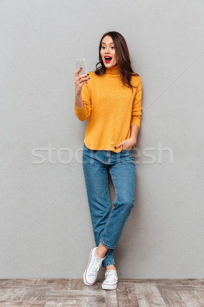 Full length image of Surprised happy brunette woman in sweater Stock photo © deandrobot