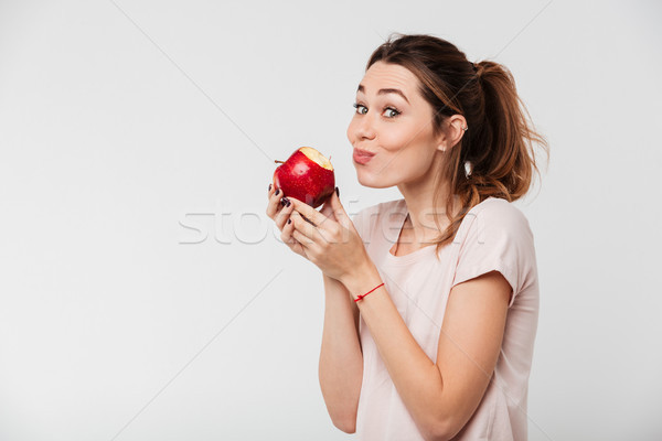 Close up portrait of a lovely girl biting an apple Stock photo © deandrobot
